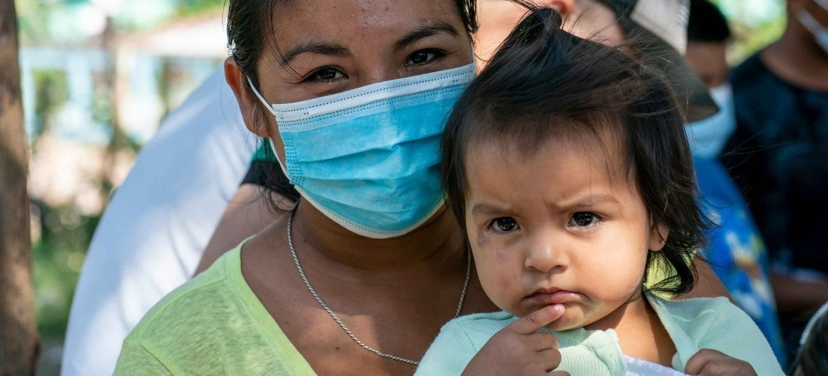 Central American mother in mask with child. Families in Central America are still coping with the effects of back-to-back hurricanes in 2020.